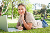 女子躺在草坪上,她的笔记本 — 图库照片