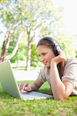 Woman with headphones and a laptop lying on the lawn — Stock Photo