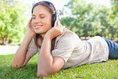 Woman enjoying music on the lawn — Stock Photo