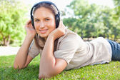 Woman listening to music on the lawn — Stock Photo