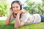 Vrouw luisteren naar muziek op het gazon — Stockfoto