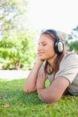 Side view of a woman enjoying music on the lawn — Stock Photo