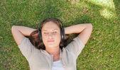 расслабленной женщина, слушать музыку, лежа на лужайке — Стоковое фото