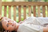Lachende vrouw liggen op een bankje — Stockfoto