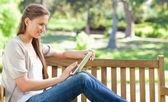 Side view of a woman using a tablet computer on a park bench — Stock Photo