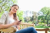 Mulher sorridente, escrevendo uma mensagem de texto em um banco do parque — Fotografia Stock