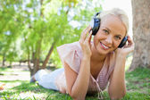 Smiling woman lying on the grass while listening to music — Stock Photo