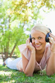 Smiling woman enjoying music on the lawn — Stock Photo