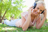 Smiling woman enjoying music on the grass — 图库照片