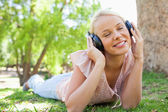 Woman wearing headphones while lying on the lawn — Stock Photo