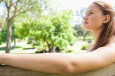 Side view of a woman sitting on a park bench — Stock Photo