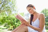 Zijaanzicht van een lachende vrouw op het gazon lezen van een boek — Stockfoto