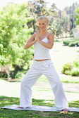 Smiling woman doing yoga exercises in the park — Stock Photo