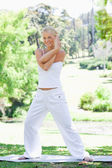 Smiling woman doing stretches in the park — Stock Photo