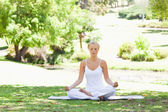 Woman sitting in a yoga position on the lawn — Stock Photo