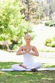 Vrouw in een yoga positie zitten op het gazon — Stockfoto
