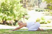 Side view of a woman doing stretches on the lawn — Stock Photo