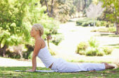 Side view of a woman doing stretches on the grass — Stock Photo
