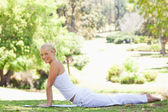 Side view of a woman doing her stretches in the park — Stock Photo
