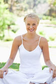 Smiling woman in a yoga position on the lawn — Stock Photo