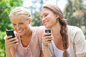 Smiling friend with cellphones — Stock Photo