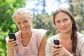 Friends with their cellphones in the park — Stock Photo