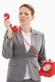 Angry businesswoman shouts at phone — Stock Photo