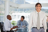 Smiling young businessman leans on table — Stock Photo