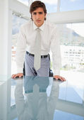 Young serious businessman leaning on a table — Stock Photo