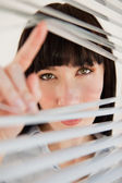 A woman looking through some blinds into the camera — Stock Photo