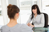 A smiling business woman listens to what the other woman has to — Stock Photo