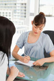As her co-worker chats the brunette employee writes on her note — Stock Photo