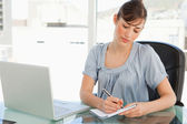 A woman takes down notes on her notepad — Stock Photo