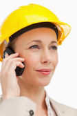 Woman on the phone wearing safety helmet — Stock Photo
