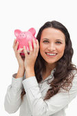 Portrait of a brunette shaking a piggy bank — Stock Photo