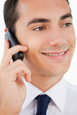 Close-up of a smiling man in a suit using his cellphone — Stock Photo