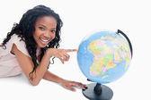 A young girl smiling at the camera has her finger on a globe — Stock Photo