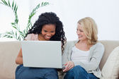 Two women with a laptop in front of them are laughing — Stock Photo
