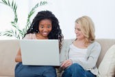 A surprised woman looking at a laptop with her friend — Stock Photo