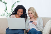 Two women are buying over the internet with a bank card — Stock Photo
