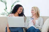 Two women looking at each other holding a bank card and a laptop — Stock Photo
