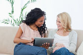 A woman holding a tablet computer is smiling at her friend — Stock Photo