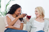 Two women holding wine glasses are smiling at each other — Stock Photo