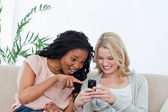 A surprised woman is pointing at a mobile phone that her friend — Stock Photo