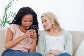 A woman is texting on her mobile phone while her friend watches — Stock Photo