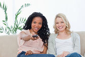 A woman with her friend is pointing a television remote control — Stock Photo
