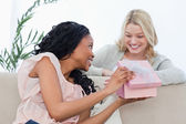 A smiling woman gets a present from her friend — Stock Photo