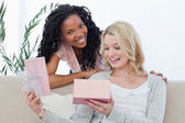 A woman opens a box containing a present and her friend smiles — Stock Photo