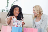 Two laughing women look at clothes they bought — Stock Photo