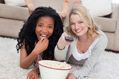 Two women lying on the ground with a bowl of popcorn — Stock Photo